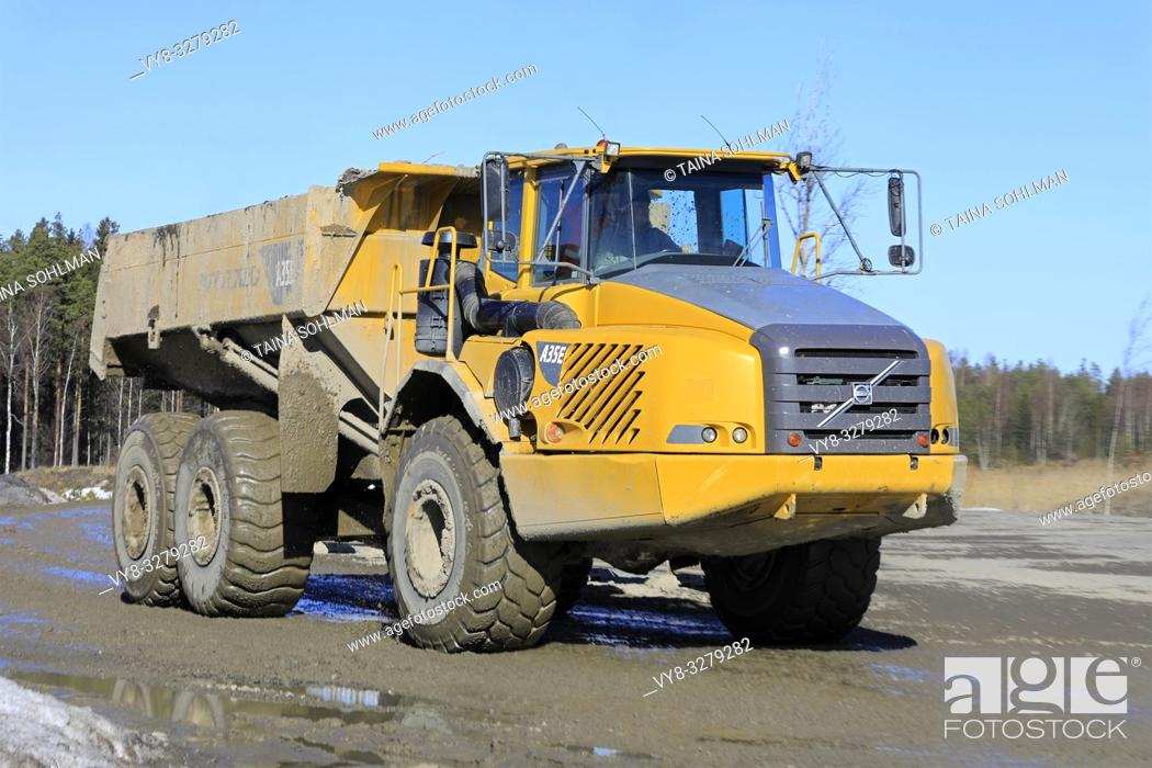 Stock Photo: Lieto, Finland - March 22, 2019: Volvo A35E articulated dumper driving at speed along dirt road by a construction site on a sunny day of spring.