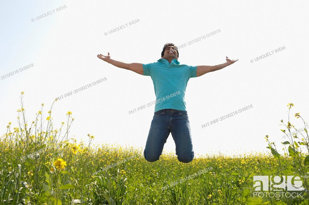 Stock Photo: Man jumping with his arm outstretched in an oilseed rape field.