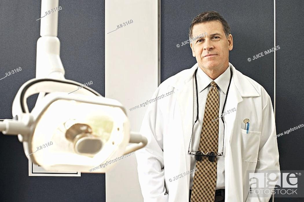 Stock Photo: Male dentist standing beside surgical light in dental surgery, smiling, front view, portrait.