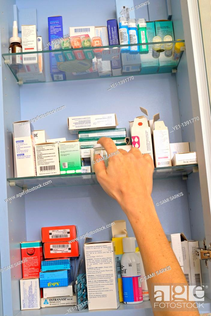 Stock Photo: Woman's hand taking medicine from a cupboard fill of prescription drugs and pharmaceuticals.