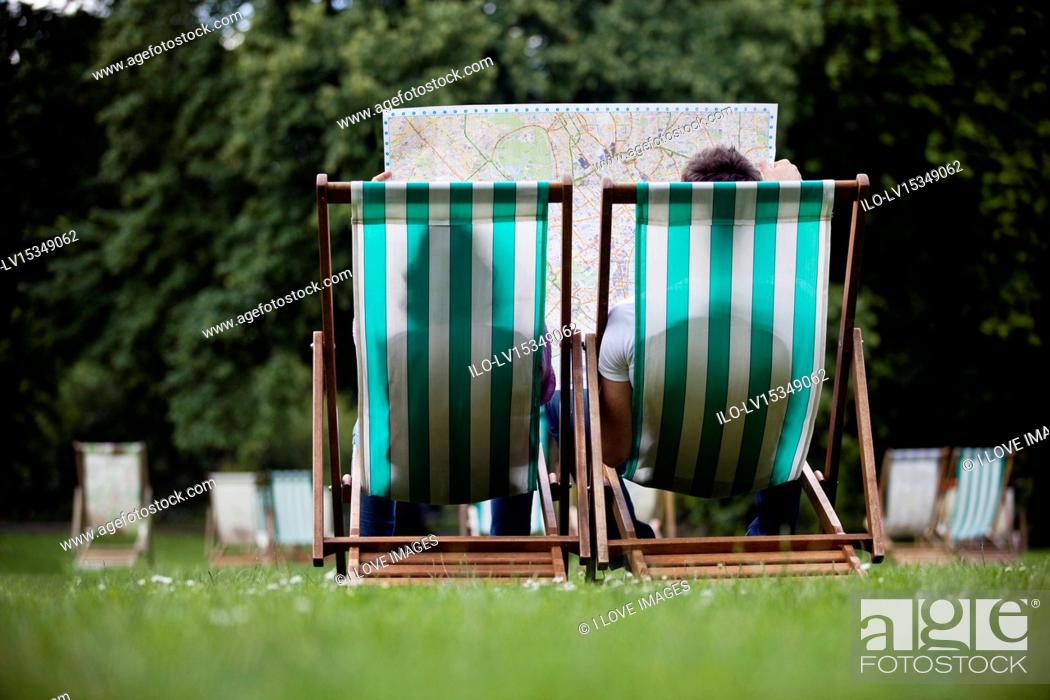 Stock Photo: A young couple sitting on deckchairs in St James Park, looking at a map.