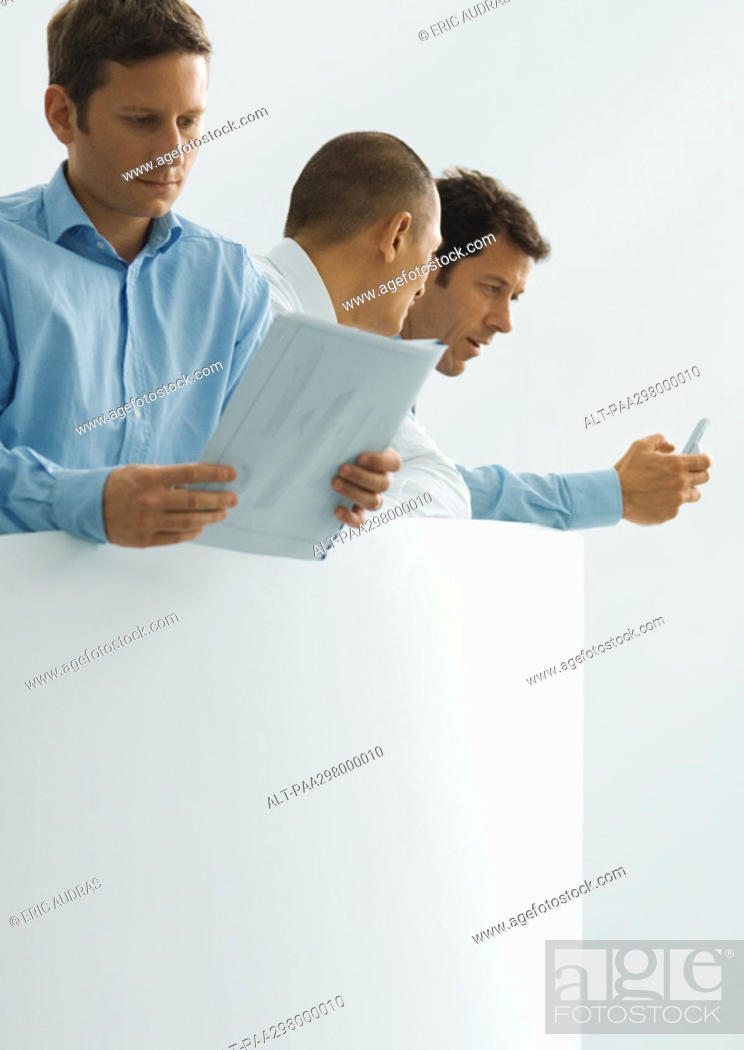 Stock Photo: Three businessmen, one holding document, other two looking at cell phone.