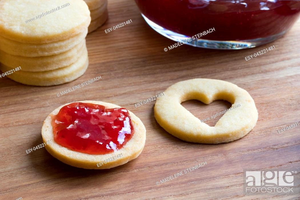 Stock Photo: Preparation of traditional Linzer Christmas cookies - filling the cookies with strawberry jam.