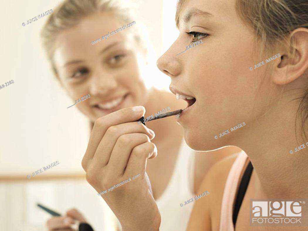 Stock Photo: Two teenage girls 15-17 applying lipstick in bathroom, smiling, close-up, side view.