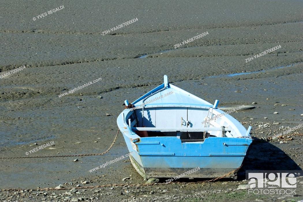 Stock Photo: Rowboat stranded on mud flat.