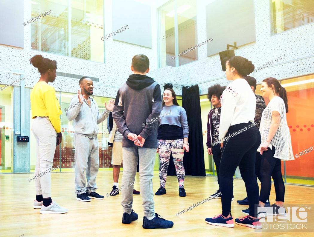 Imagen: Teenage students listening to male instructor in dance class studio.