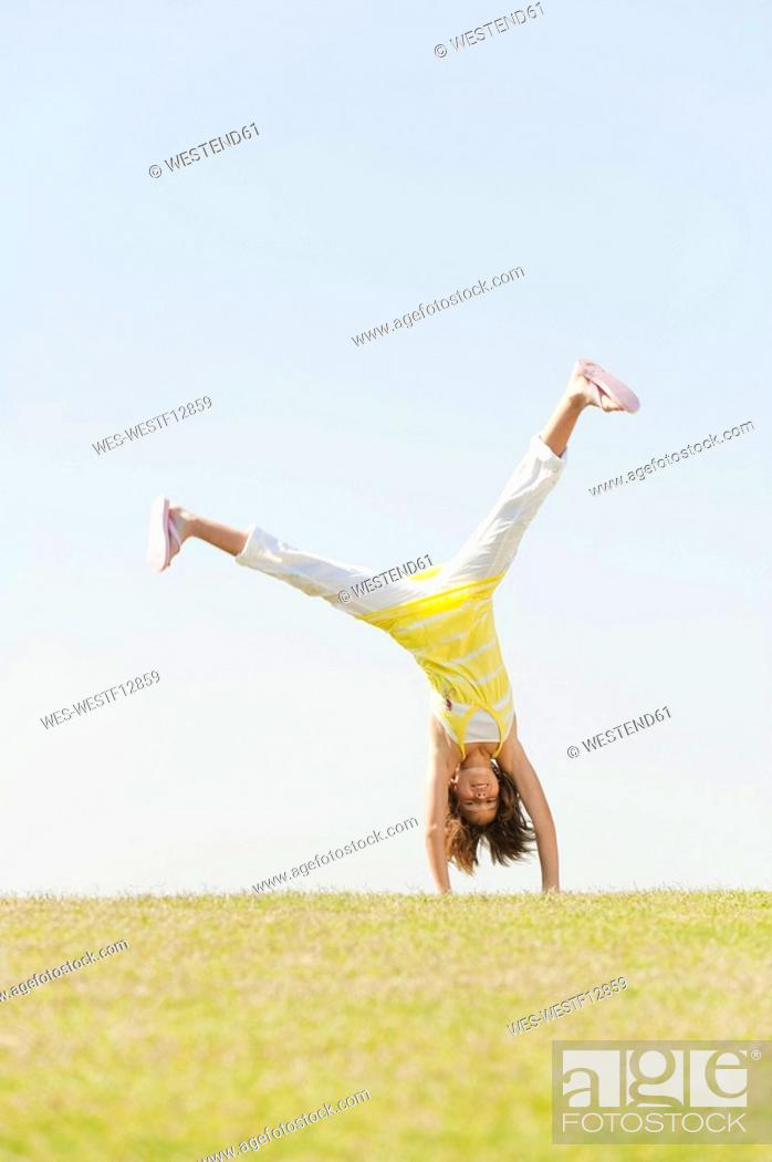 Stock Photo: Spain, Mallorca, Girl 10-11 doing cartwheel in meadow.