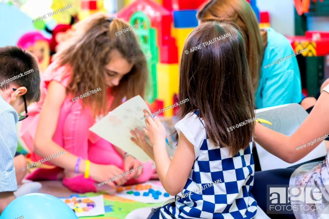 Stock Photo: Group of kids applying colorful plasticine on various drawings printed on paper sheets during educational activity in the classroom of a modern kindergarten.