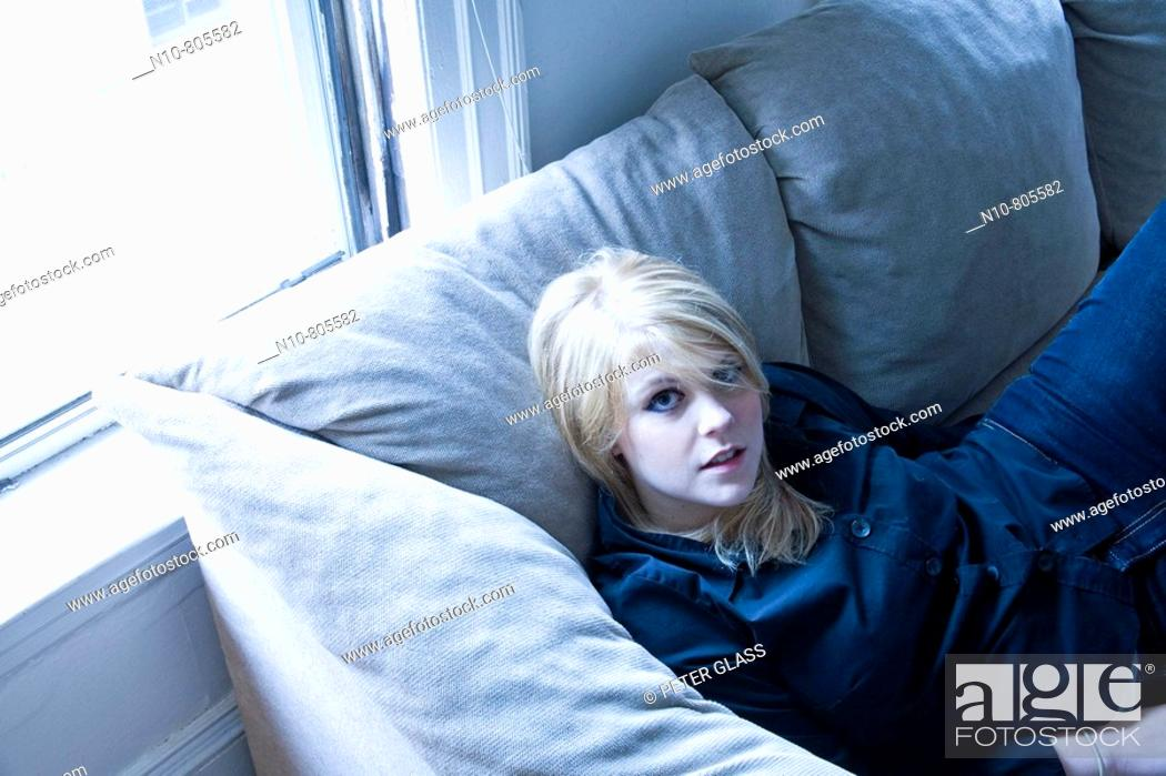 Stock Photo: Young blond woman sitting on her living room sofa.