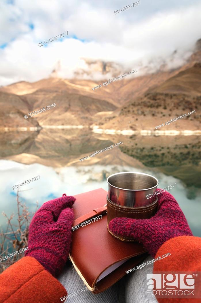 Photo de stock: A first-person view of women's hands in coats and mittens are holding a metal mug with tea or coffee and a leather pocket diary against the backdrop of a.