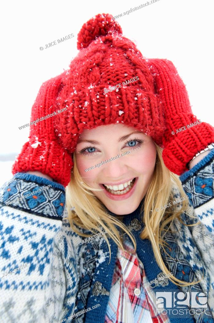 Stock Photo: A portrait of a young woman wearing a red woolen hat and gloves.
