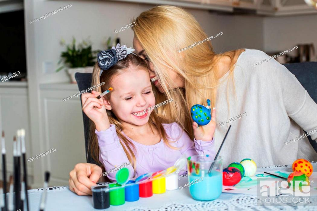 Stock Photo: Loving mother and her daughter painting easter eggs. Cozy home atmosphere. Easter.