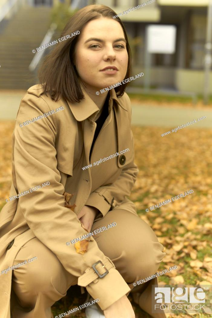 Stock Photo: young woman crouching outdoors with autumn leaves, wearing coat, in Munich, Bavaria, Germany.