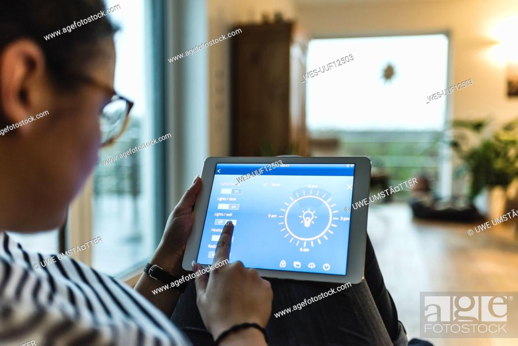 Stock Photo: Woman using tablet with smart home control functions at home.