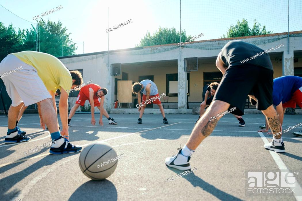 Stock Photo: Friends on basketball court warming up.