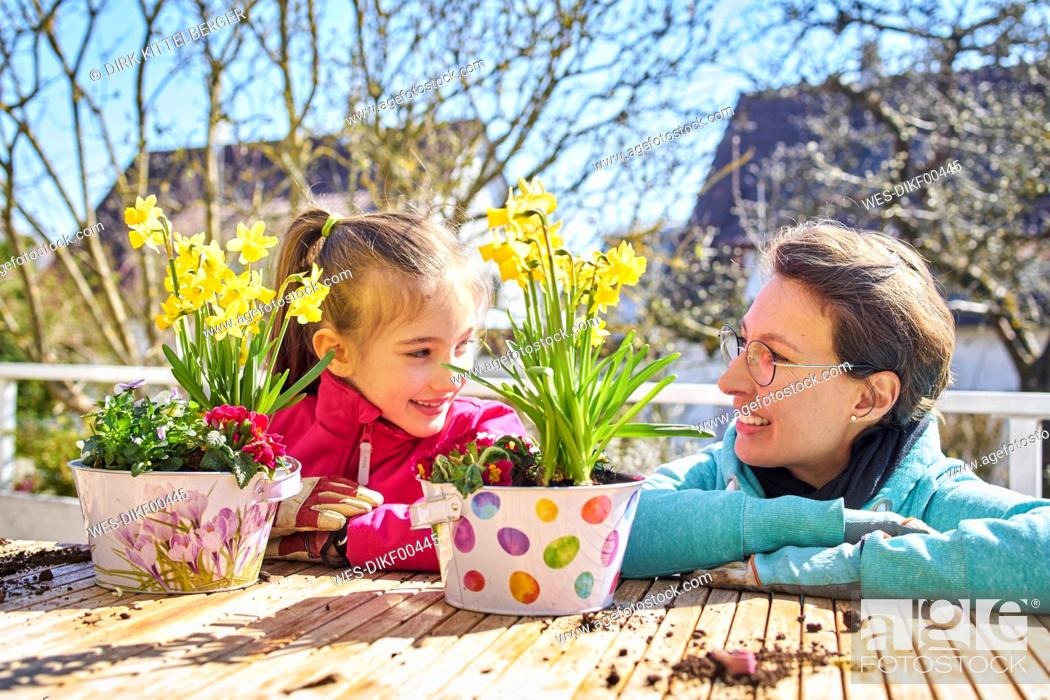 Stock Photo: Mother and daughter planting flowers on balcony.