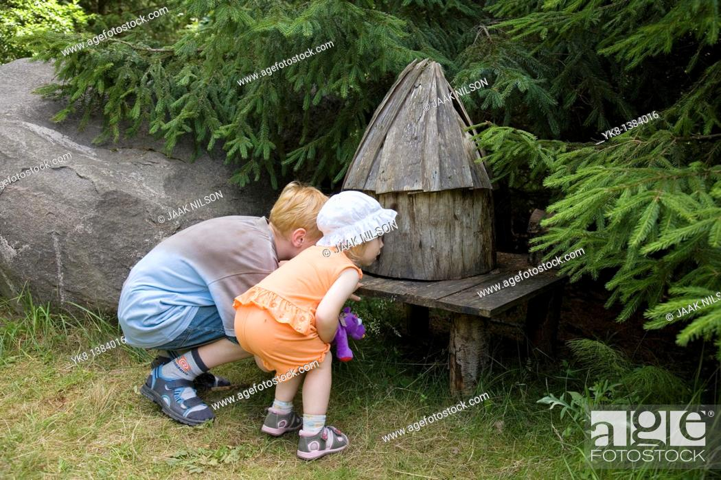 Stock Photo: Kid Girl and Boy Looking Small Fairy-Tale House at Pokumaa, Võru County, Estonia.