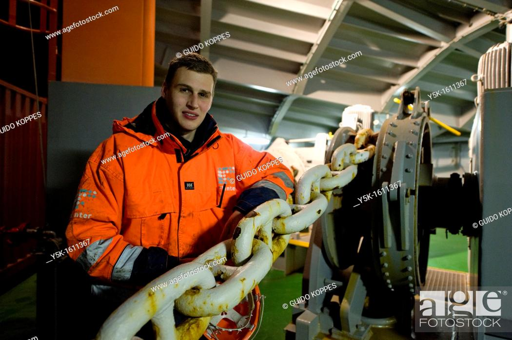 Stock Photo: The Dutch Cadet at container-vessel MV Flintercape, on the prow or front of the ship. He leans against the chains, connected to the ships anchor.