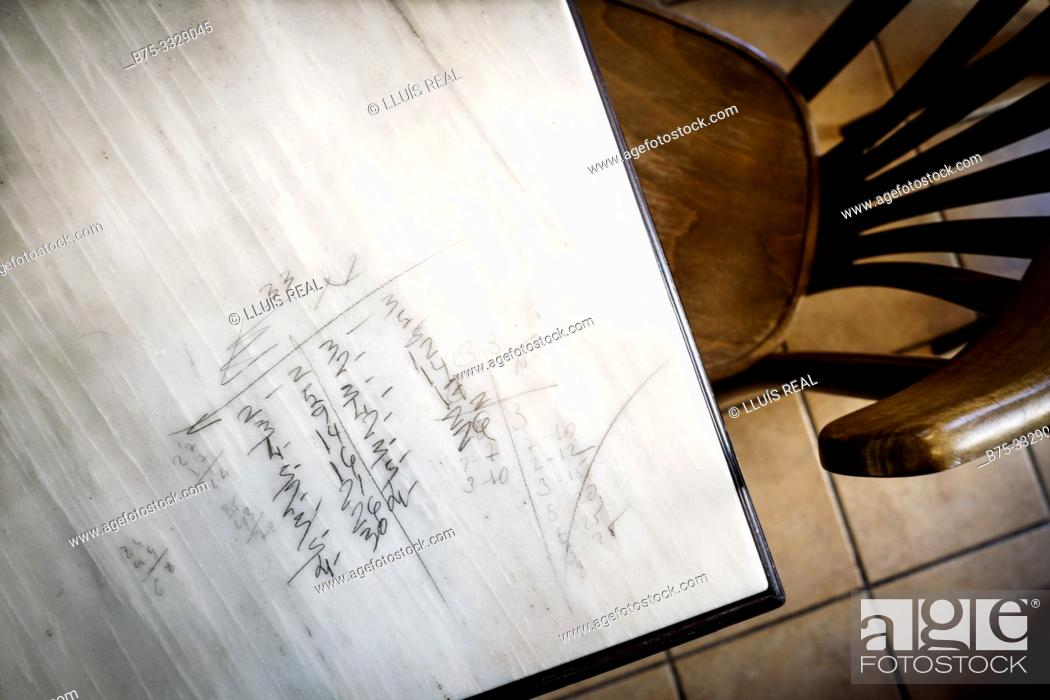 Stock Photo: Closeup of a marble table with pencil inscriptions of a domino game, and a chair next to Mahon, Baleares, Spain, Europe.