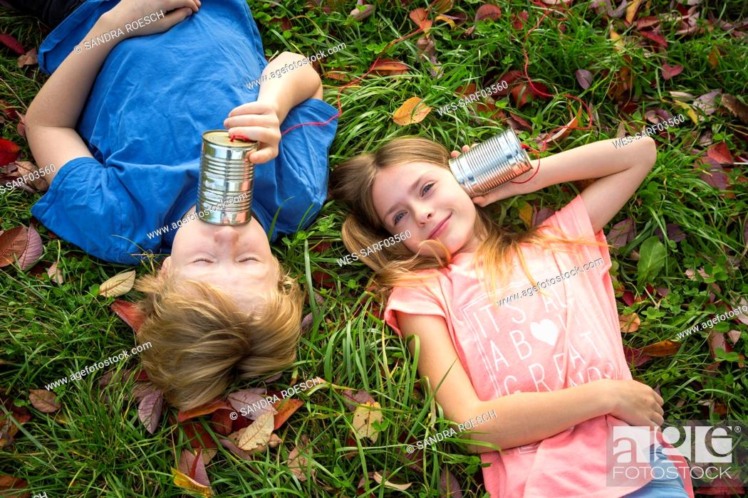 Stock Photo: Boy and girl on a meadow having fun with tin can phone.