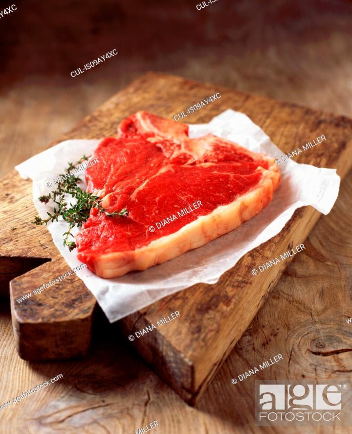 Stock Photo: Food, meat, beef, t-bone steak, on rustic wooden chopping board.