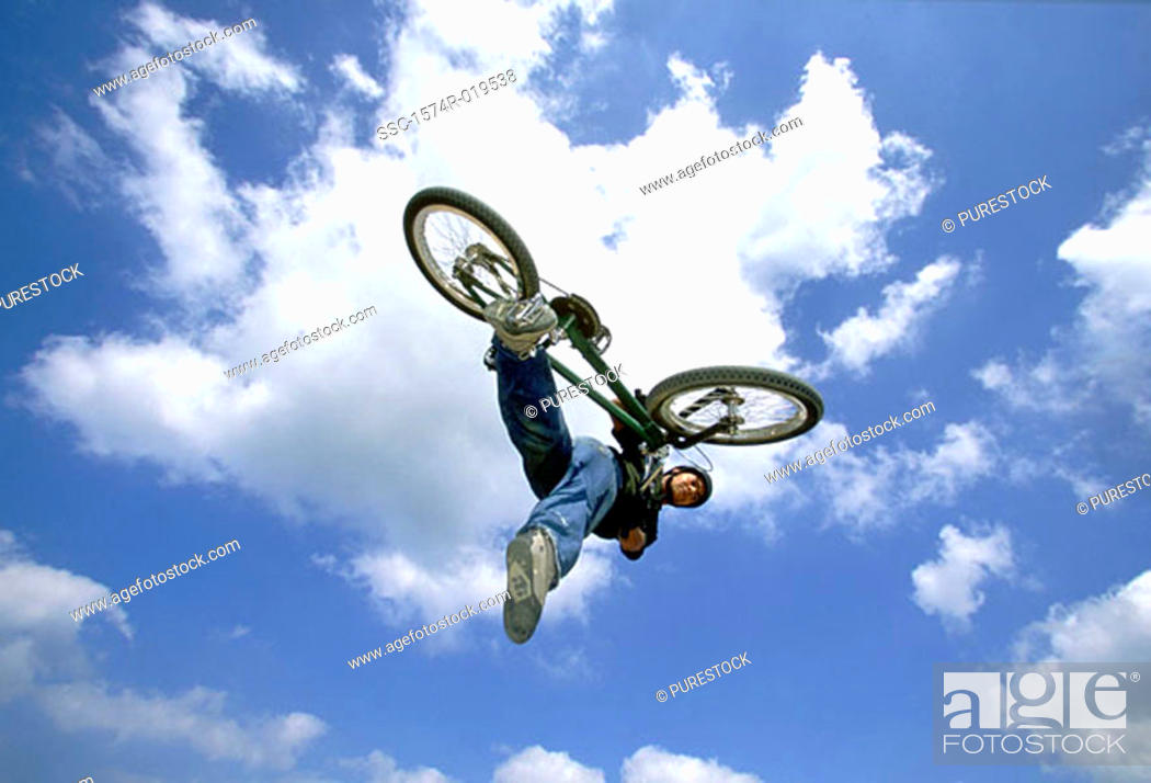 Stock Photo: Young man performing stunt on bicycle.