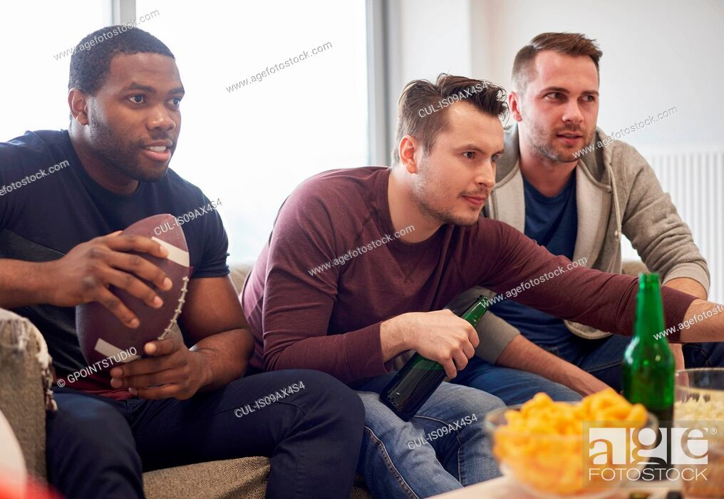 Stock Photo: Group of men holding ball watching sports event on television with snacks and beers.
