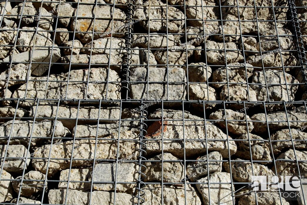 Stock Photo: Wire mesh protecting stone wall.