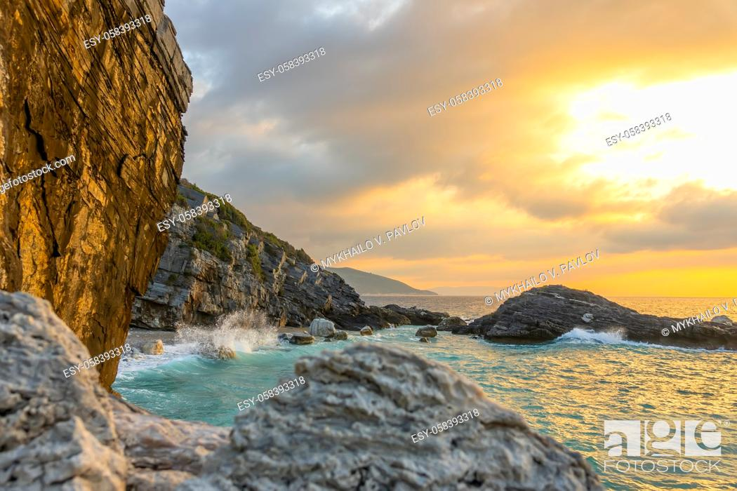 Imagen: Summer evening and a small beach on a rocky beach. Wave smashes on coastal rocks with lots of splashes.