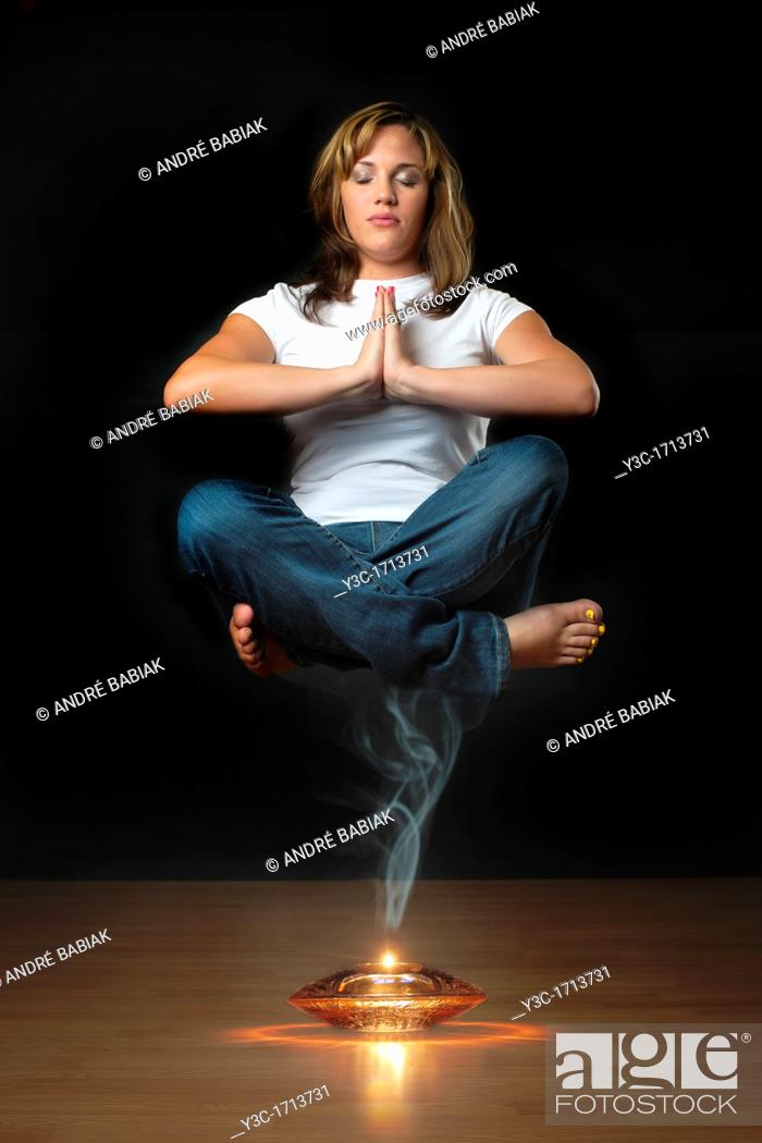 Stock Photo: Genie levitation - woman floating in air over smoking oil lamp.