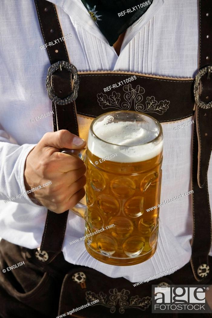 Stock Photo: Detail of man in traditional Bavarian, Lederhosen, holding litre glass of beer.