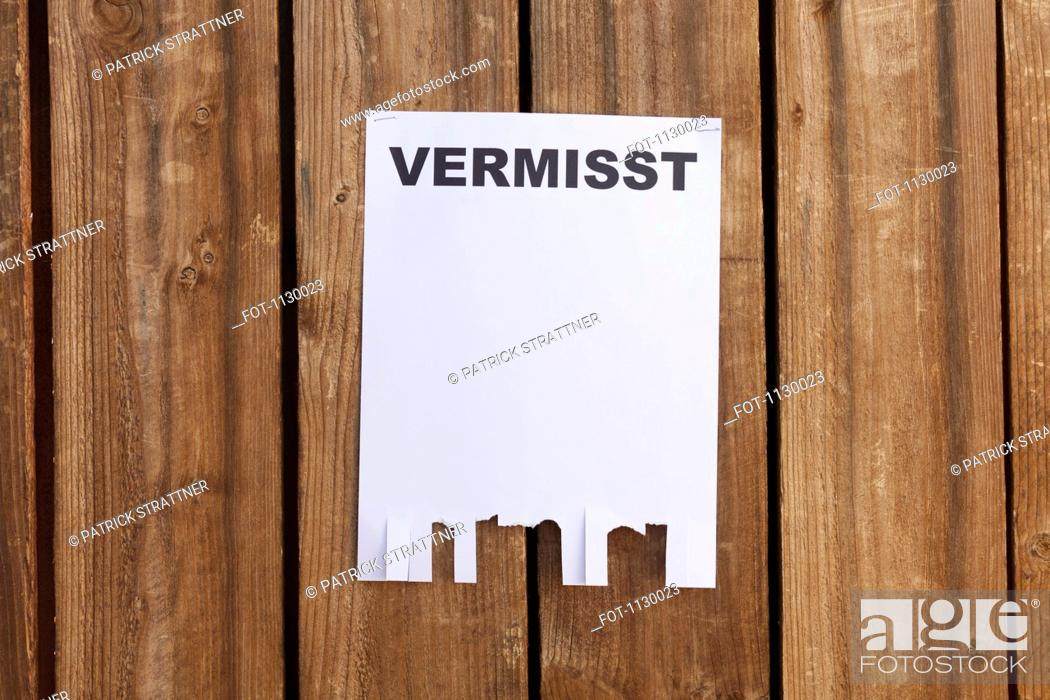 Stock Photo: A flyer posted on a wooden fence with the German word for missing on it.