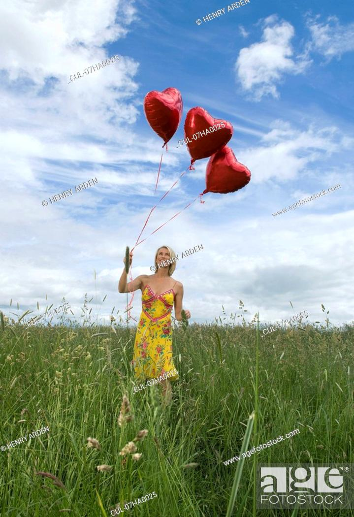 Stock Photo: Smiling woman in field with balloons.