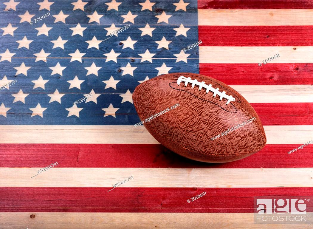 Photo de stock: American football on rustic wooden USA flag.