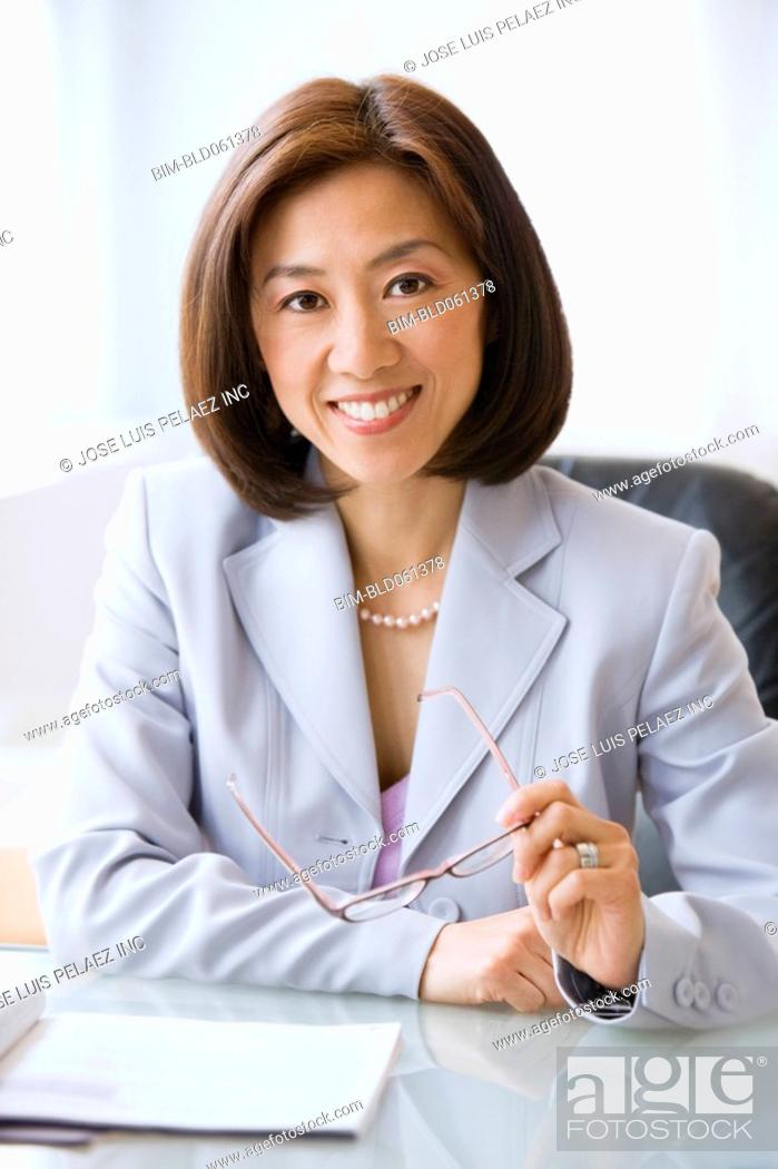 Stock Photo: Asian businesswoman holding eyeglasses.
