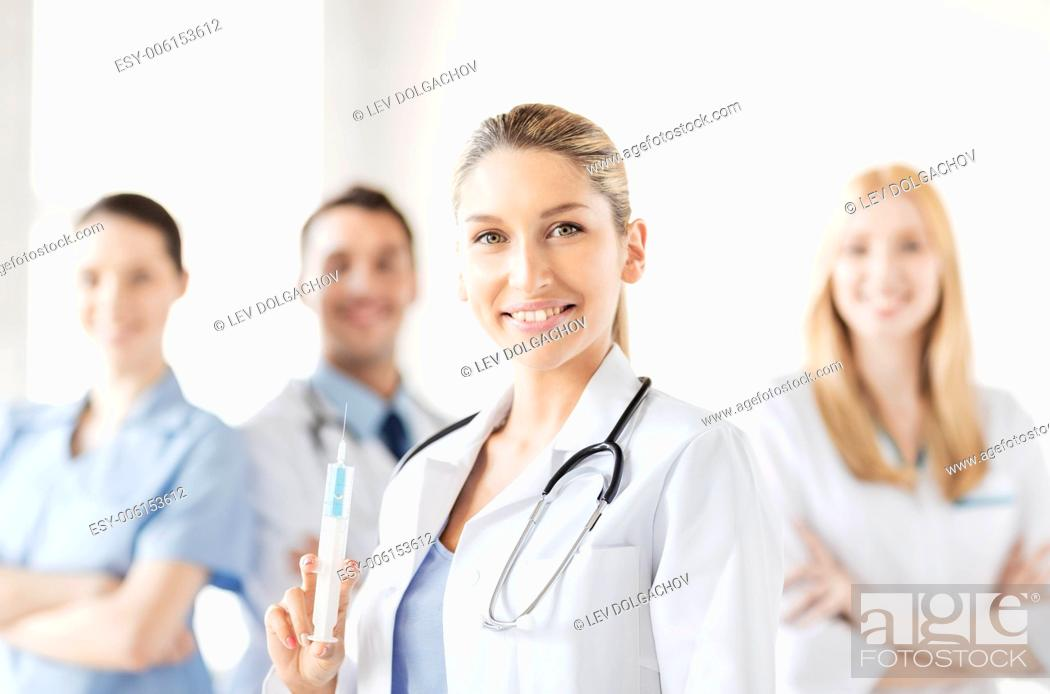 Stock Photo: healthcare and medicine concept - group of medics with female doctor holding syringe with injection.
