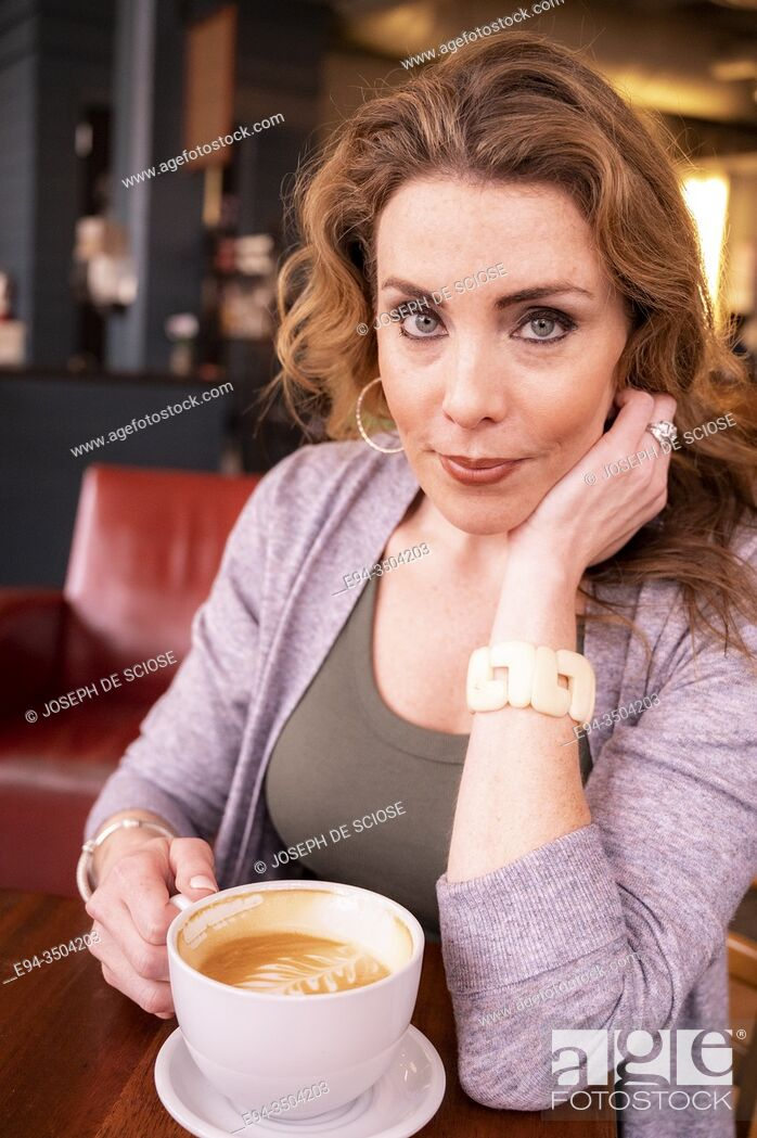 Photo de stock: A pretty 37 year old redhead woman in a holding a large cup of coffee in a cafe.