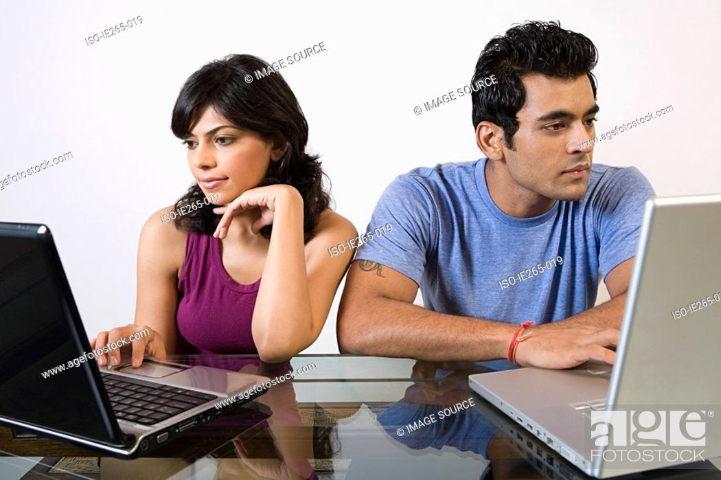 Stock Photo: A couple using alaptops.