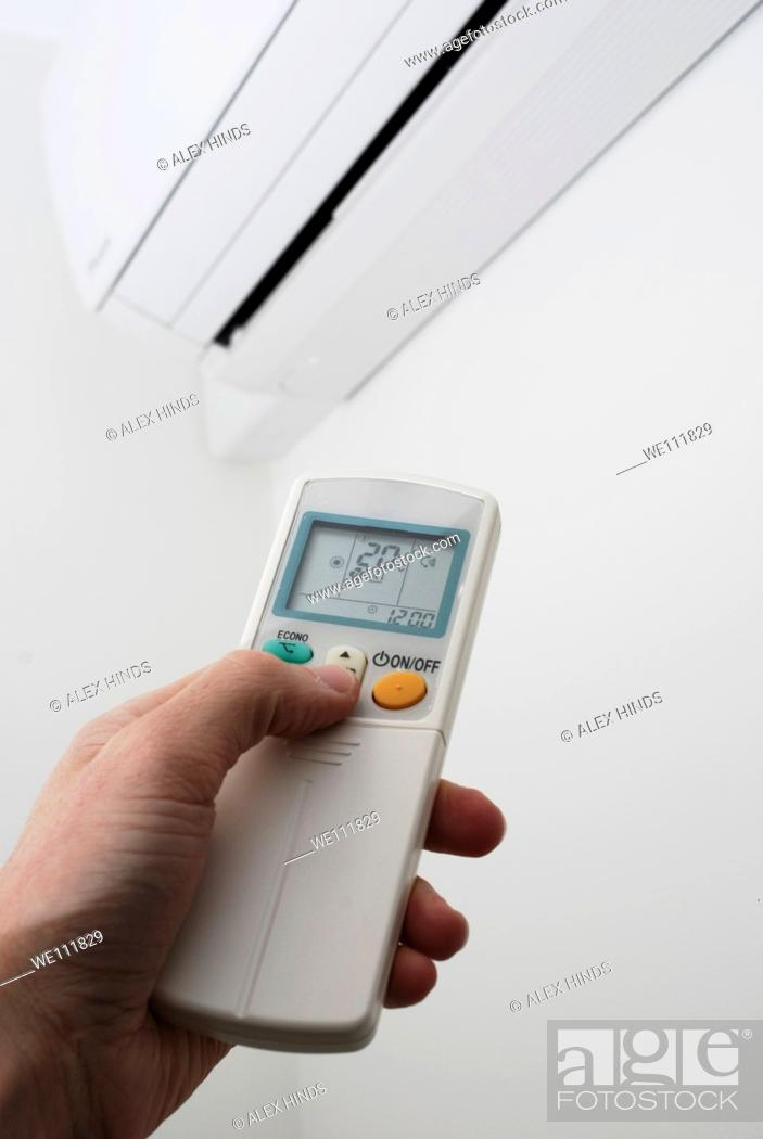 Stock Photo: Adjusting the settings on a wall mounted air conditioning unit.