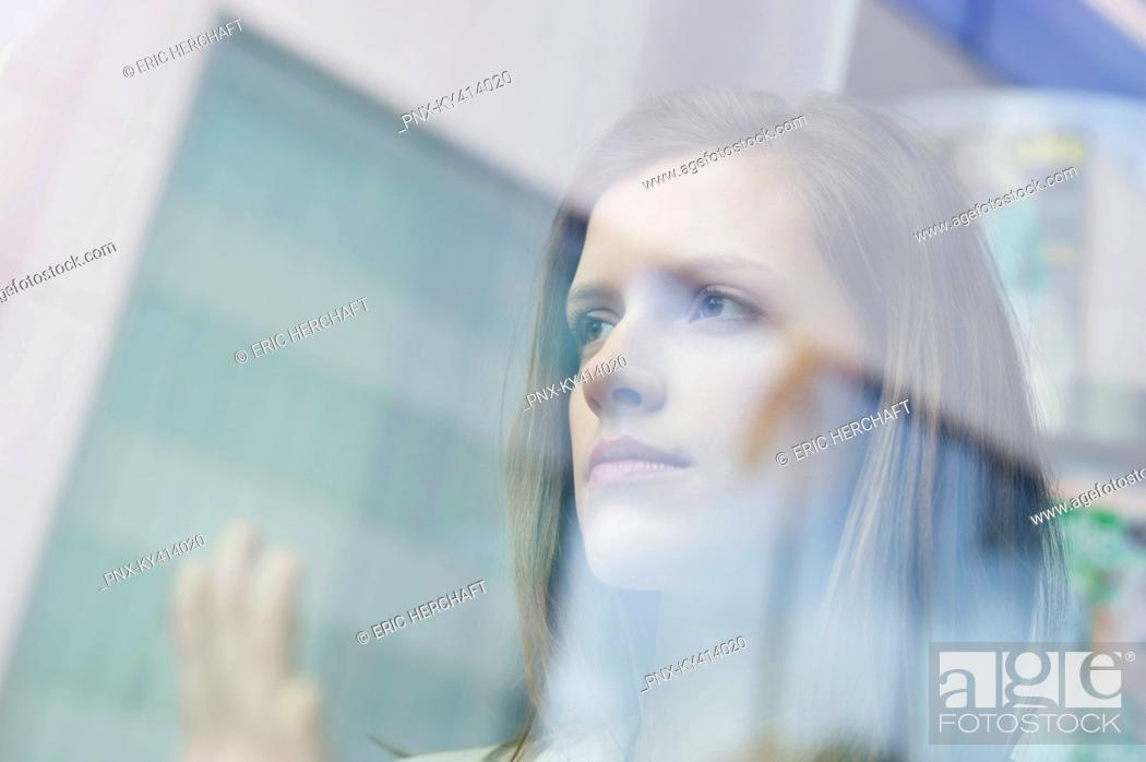 Stock Photo: Businesswoman looking through the glass of a window.