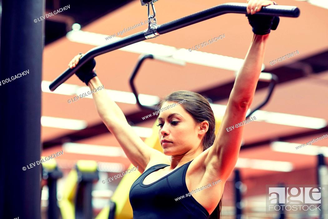 Stock Photo: sport, fitness, bodybuilding, lifestyle and people concept - woman flexing arm muscles on cable machine in gym.