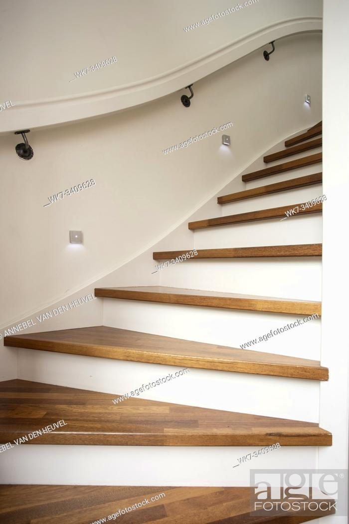Stock Photo: Modern steel staircase with wooden steps in a new apartment in a residential building with spots light in wall close-up.