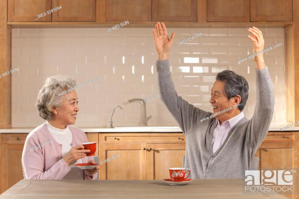 Stock Photo: Happy old couple drinking tea and having conversation in the kitchen, Chinese ethnicity.