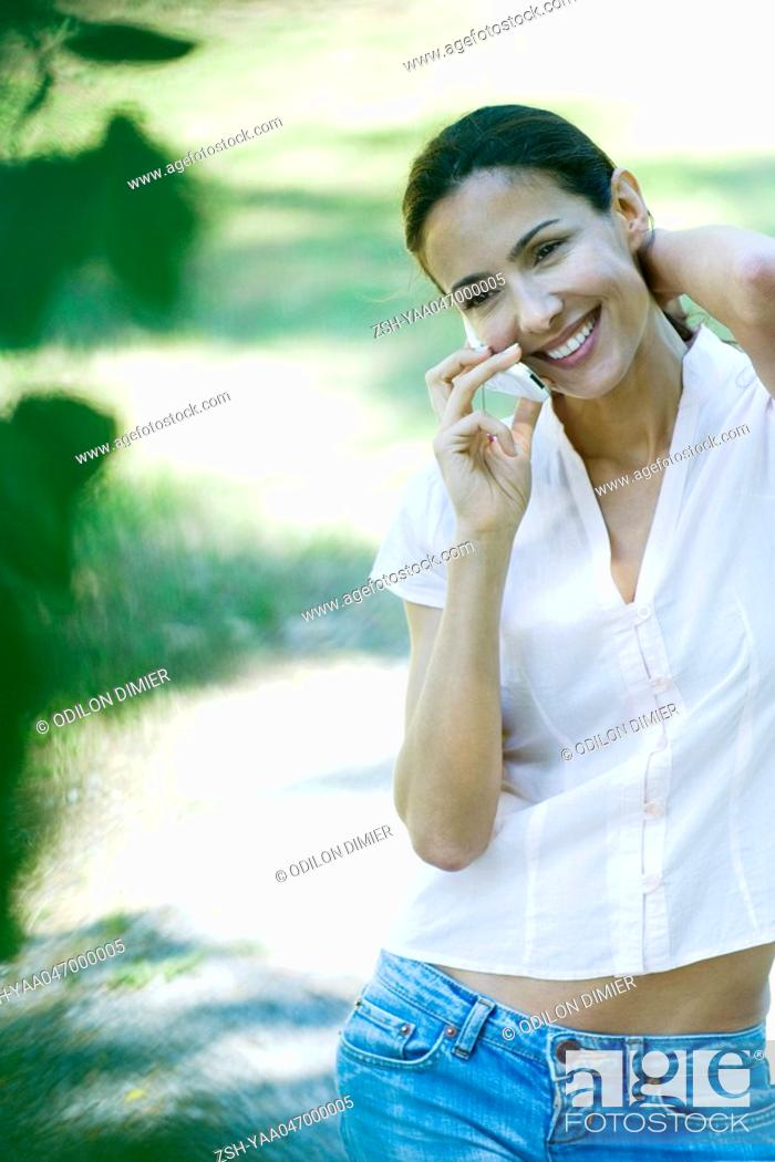 Stock Photo: Woman using cell phone outdoors, smiling.
