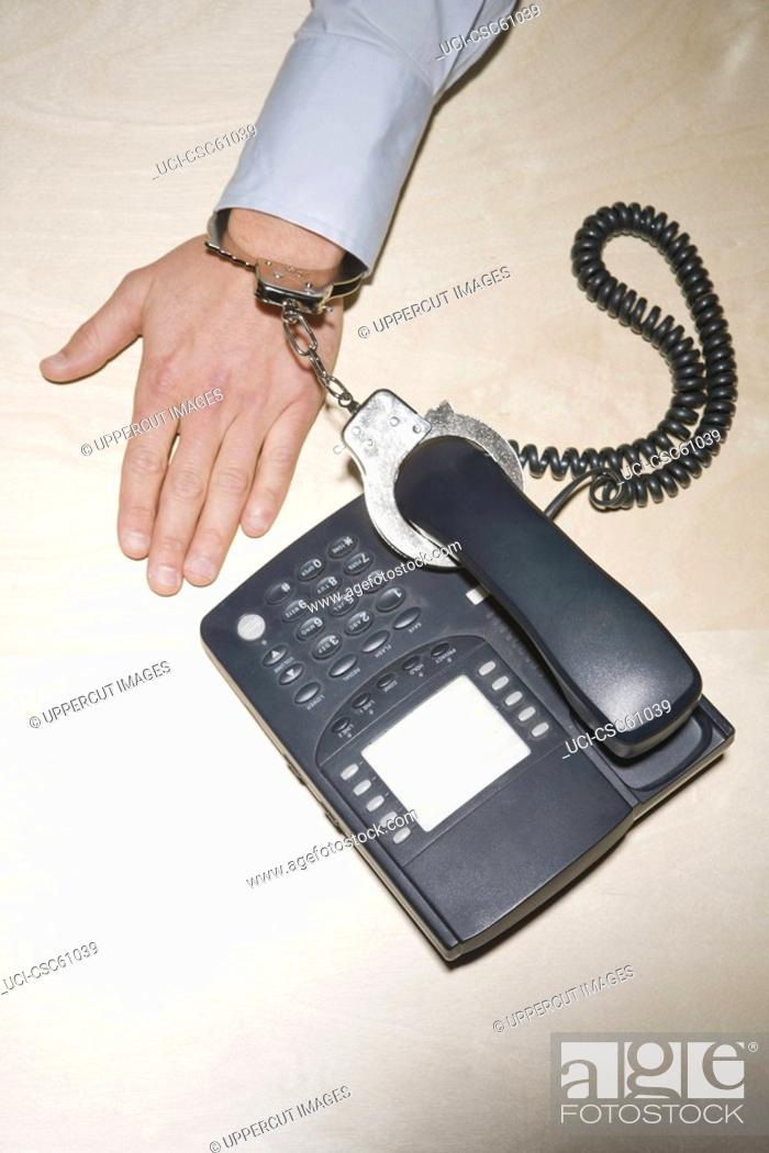 Stock Photo: Businessman handcuffed to telephone.