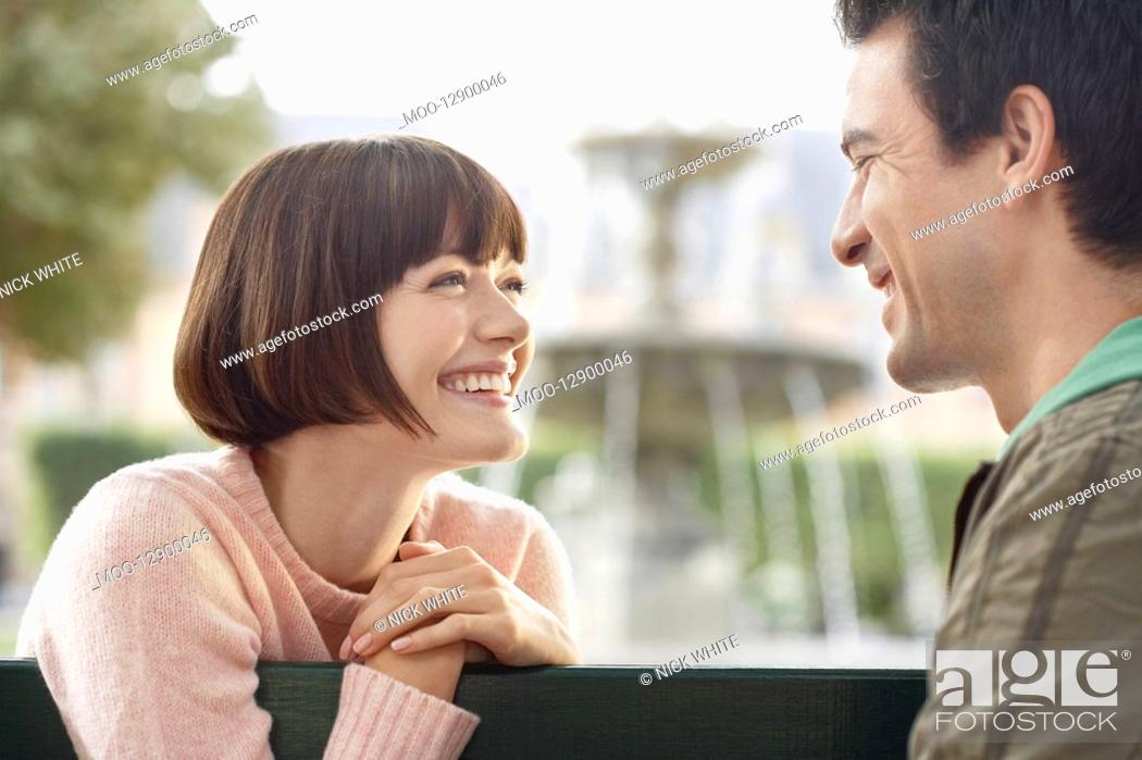 Stock Photo: Couple smiling at each other on bench in front of fountain head and shoulders.