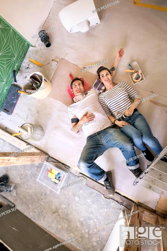 Stock Photo: Happy couple renovating new home, taking a break, daydreaming.