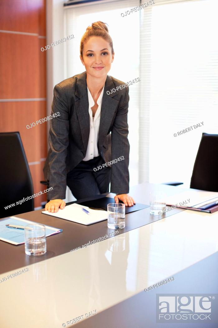 Stock Photo: Portrait of smiling businesswoman leaning on table in conference room.