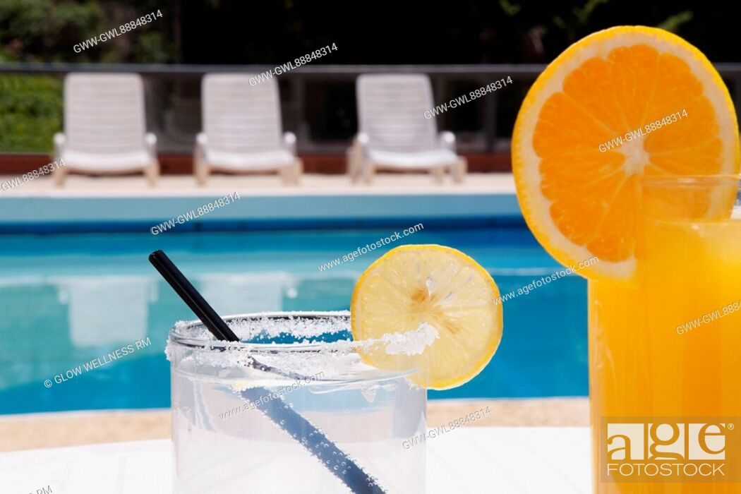 Imagen: Lounge chairs with juices on table at the poolside.