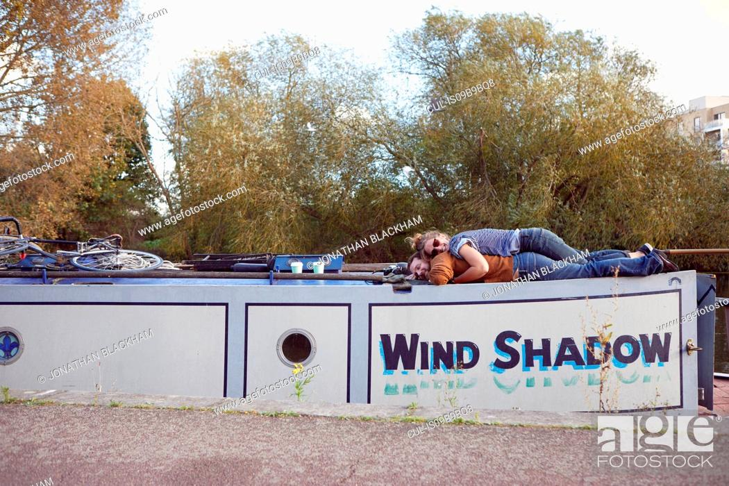 Stock Photo: Couple lying on roof of canal boat.